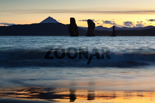 Three Brothers Rocks in Pacific Ocean at sunset. Russian Far East, Kamchatka Peninsula