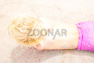 Close Up Of Blond Caucasian Toddler Boy Playing On A Sunny Sandy Beach