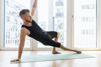 Young handsome man practicing yoga at home