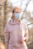 Portrait of caucasian sporty woman wearing medical protection face mask while walking in park, relaxing and listening to music. Corona virus, or Covid-19, is spreading all over the world