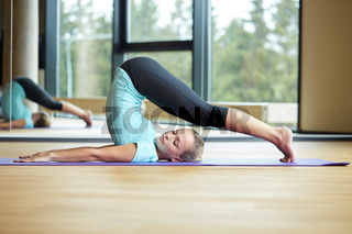 smiling woman stretching on mat in gym