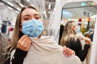 Kundin mit Mundschutz in der Umkleide einer Boutique
