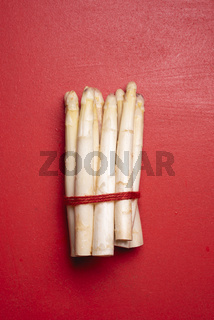 White asparagus on a red table, top view. Fresh vegetables