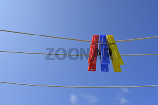 Clothesline with clothespins against blue sky