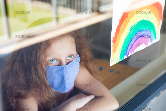 Girl wearing face mask looking out to the window