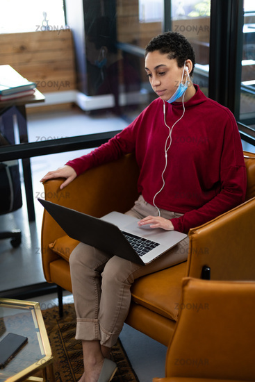 Mixed race woman wearing lowered face mask using laptop and earphones video conferencing in office