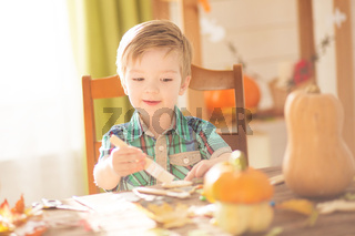 Happy Halloween concept. Cute little happy boy carving a pumpkin and decorated cookies for halloween on table indoors.