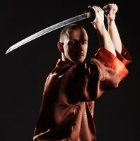 Man in chinese costume with sword studio portrait