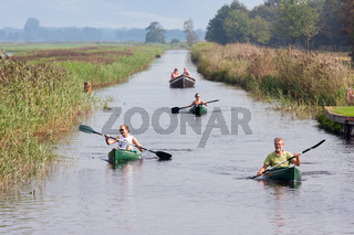 People pedaling in canoes through wetlands Dutch National Park Weerribben