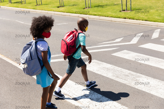 Two kids wearing face masks crossing the road