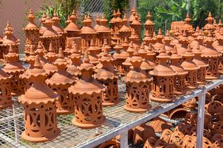 Many orange clay lanterns outside at pottery