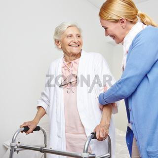 Krankenpfleger hilft Seniorin mit Gehhilfe