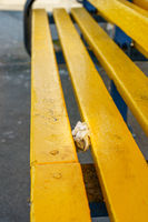 Pair of used nitrile medical gloves shoved in between slats on public seating during Coronavirus Covid-19 pandemic
