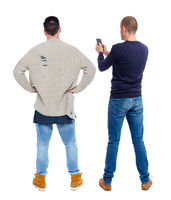Back view of two man in sweater with mobile phone.