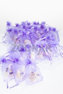 S-foermig arrangierte Bodybutter in lila Chiffonsaeckchen