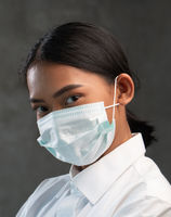 Young Asian woman wearing virus protection mask isolated over concrete wall background