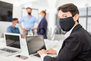 Junger Business Mann mit Mundschutz am Laptop