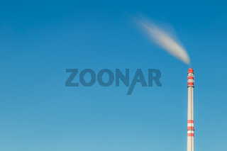 Smoke from a tall chimney in the clear sky