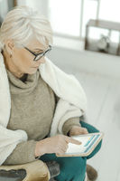 Old Woman In Glasses Is Sitting At Home On The Leather Sofa With A Tablet in Her Hand