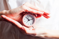 Woman holding alarm clock with both hands
