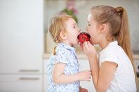 Zwei Kinder essen gemeinsam einen roten Apfel