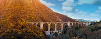 Picturesque panoramic image arched old bridge located in French Pyrenees and rocky mountain range view, blue cloudy sky, sunny day. Europe
