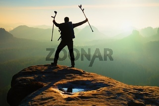Tourist with  medicine crutch above head achieved mountain peak. Hiker with broken leg in immobilizer.