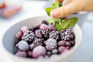 Female hand holding a mint leaf on a bowl of blackberries