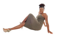 Pretty African female sitting on the floor in a gray dress