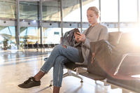 Casual blond young woman using her cell phone while waiting to board a plane at airport departure gates. Empty airport terminal due to corona virus pandemic