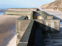 concrete stairs on seawall in blackpool with the beach at low tide in sunlight