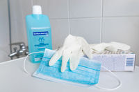 GERMANY - MARCH 22, 2020: Virus und Bacteria prevention equipment. Surgical Mask, gloves and hand sanitizer for hygiene against coronavirus pandemic.