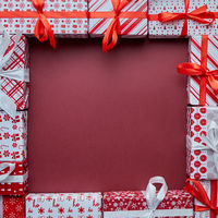 Arranged Gifts boxes wrapped in colorful festive paper with on burgund background