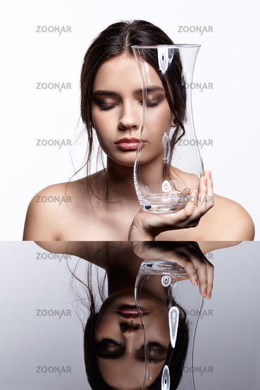 Girl hides her face behind a glass vase. Beauty portrait of young woman at the mirror table with eyes closed.
