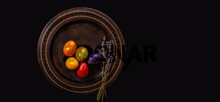 Colored easter Eggs in a plate with black background and copy space. With grass
