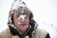 The frozen man in winter snow fell on his face. The first snow fell. A man in a fur hat in cold weather.