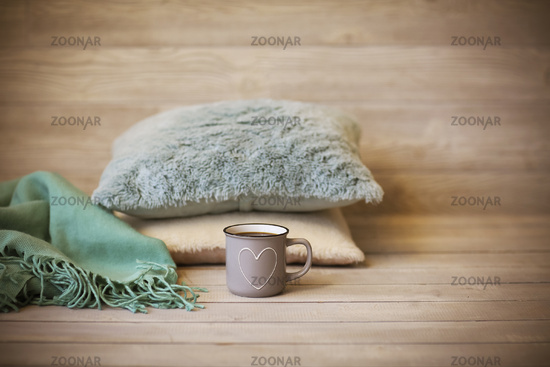 Comfortable background with cushions and mug of hot drink in cozy living room
