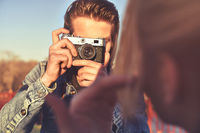 Young cheerful man photographer taking pictures with camera