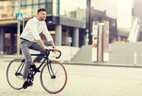 man with headphones riding bicycle on city street