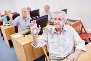 Senioren lernen und antworten auf Fragen im Computerkurs der Volkshochschule