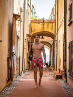 Handsome muscular shirtless man walking on old alley