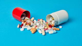 Offene Kapsel mit vielen bunten Medikamenten