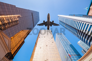upward view of airplane and modern building
