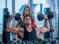 Girl insures guy during exercising with dumbbells