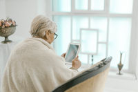 Old Grey-haired Female Relaxing At Home With A Tablet in Her Hand.