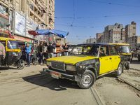 A black and yellow antiquated Lada taxi driving through the beaten road in Alexandria