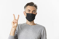 Concept of covid-19, social distancing and quarantine. Close-up of cheerful middle-aged guy in medical mask, showing peace sign and smiling, standing over white background