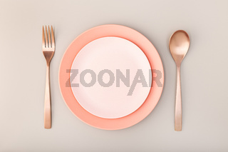 Empty Plate, fork and knife on Table. Pink Pastel tones. Mock up