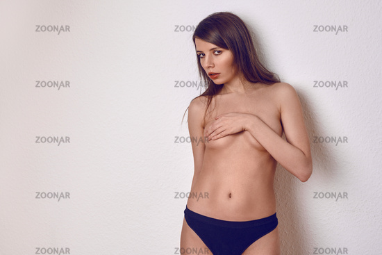 Topless sexy young woman covering her breast