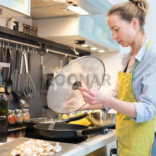 Stay at home housewife woman cooking in kitchen, stir frying dish in a saucepan, preparing food for family dinner.